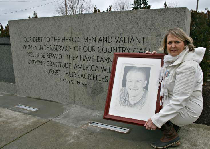 Monica McNeal holds Mike Reagan's portrait of her son, Eric Ward Reagan.